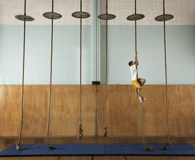 A child climbing up a rope in a school gym. - MINF03187