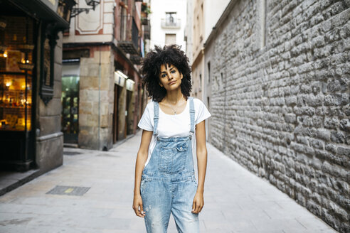 Spain, Barcelona, portrait of woman with curly hair wearing dungarees - JRFF01730