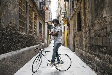 Spain, Barcelona, man standing with racing cycle in an alley - JRFF01733