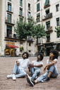 Spain, Barcelona, three friends sitting on a square looking up - JRFF01736