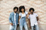 Portrait of three friends wearing denim standing in front of brick wall - JRFF01763