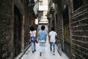 Spain, Barcelona, back view of three friends walking down an alley - JRFF01769