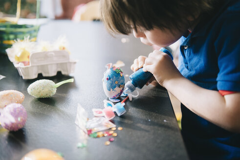 A child decorating eggs at Easter with glitter, glue and paint. - MINF03335