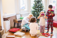 A mother and three children on Christmas morning opening presents. - MINF03401
