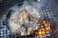 An outdoor cookout, a game birds in a pan surrounded by mirepoix of vegetables above a glowing fire. - MINF03473