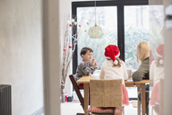 Three children, one in a Santa hat, and an adult woman seated at a table, by a large glass door with a view into the garden. - MINF03509