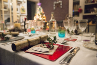 A table laid for a Christmas meal, with silver and crystal glasses and a Christmas tree in the background. - MINF03614