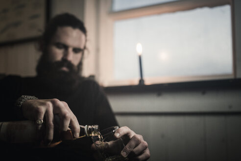 A man sitting alone in a room pouring himself a glass of whisky. A lit candle. - MINF03665