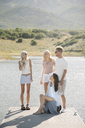 Man, woman and their two blond daughters standing on a jetty. - MINF03854