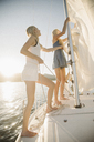 Portrait of two blond sisters on a sail boat. - MINF03890