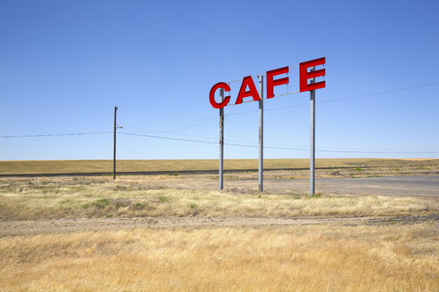 Large red capital letters on metal poles advertising cafe in a prairie. - MINF03917