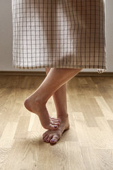 Woman wearing checkered apron standing barefoot on parquet, partial view - BZF00446