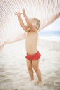 Toddler raising arms to catch striped towel - ISF19620