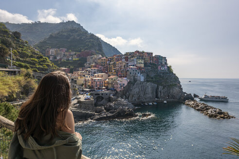 Italy, Liguria, La Spezia, Cinque Terre National Park, young woman looking to Manarola - RPSF00213