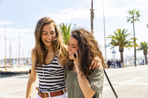 Two happy female friends with cell phone at waterfront promenade - WPEF00745