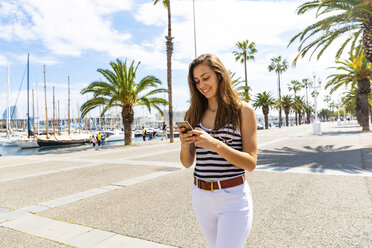 Smiling young woman looking at a smartphone at waterfront promenade - WPEF00751