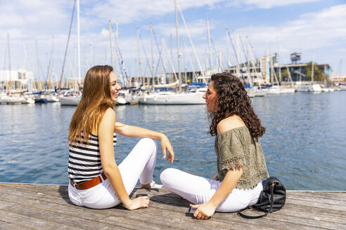 Two happy female friends talking at a marina - WPEF00754