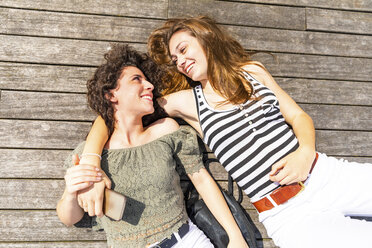 Two happy female friends lying down on a wooden floor - WPEF00757