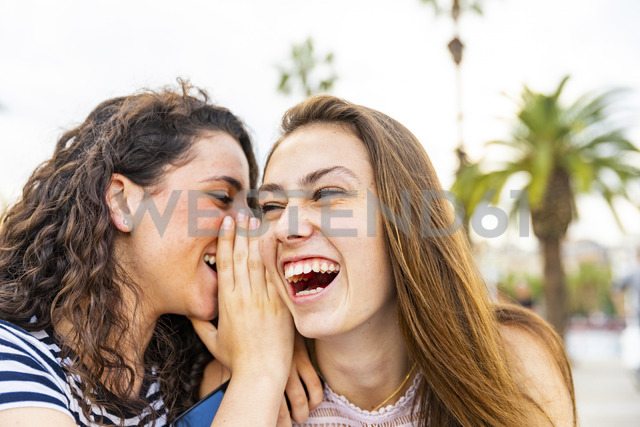 Two happy female friends whispering and laughing - WPEF00769