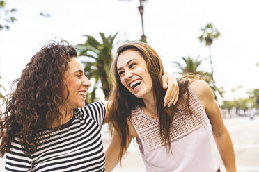 Two happy female friends on promenade with palms - WPEF00772