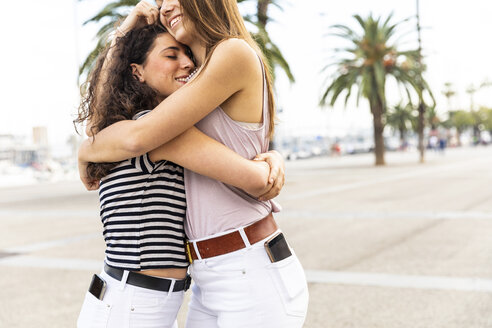 Two happy female friends embracing and hugging on promenade with palms - WPEF00775