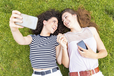 Two happy female friends lying down on grass taking a selfie - WPEF00778