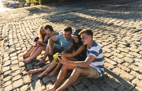 Group of friends sitting on cobblestones with refreshing drinks and cell phones - UUF14809