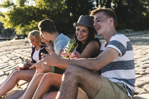 Group of friends sitting on cobblestones with refreshing drinks and cell phones - UUF14812