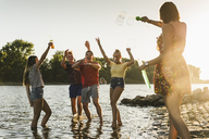 Group of happy friends in a river at sunset - UUF14818