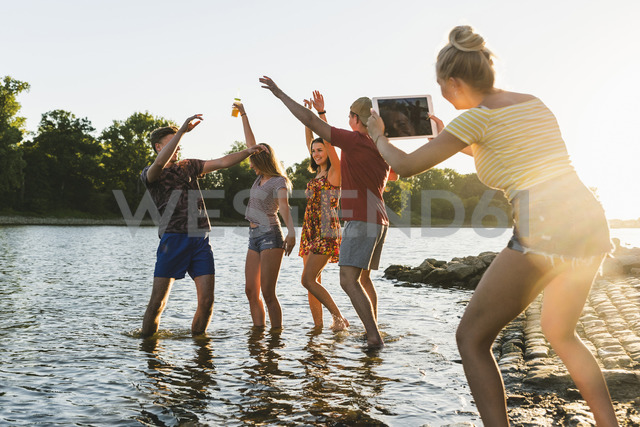 Group of happy friends with tablet in a river at sunset - UUF14821
