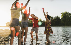 Group of happy friends having fun in a river at sunset - UUF14830