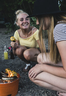 Two happy young women having a barbecue - UUF14833