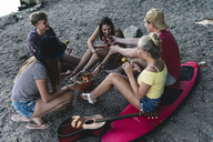 Group of friends sitting together having a barbecue - UUF14836