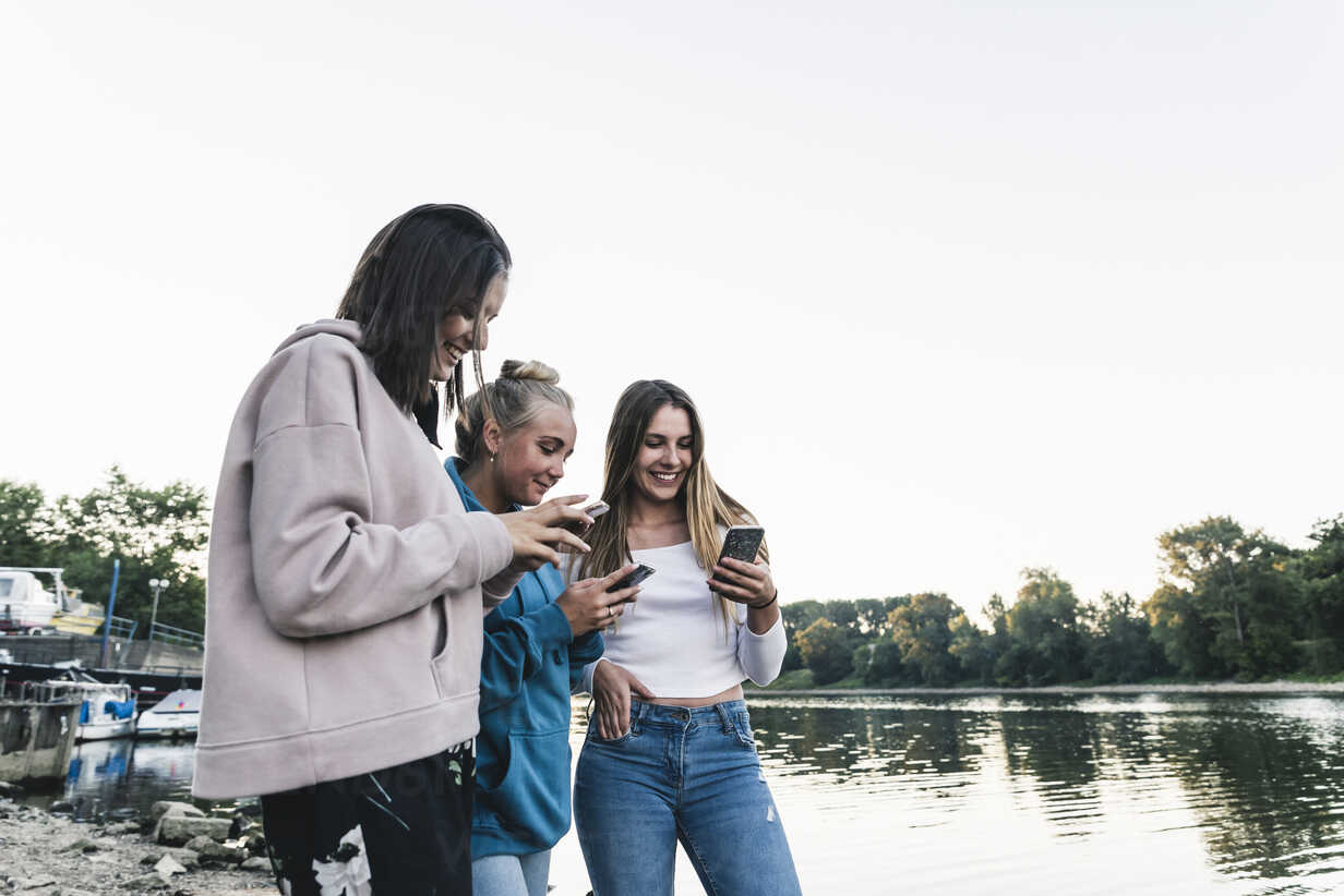 Three young women using cell phones at the riverside - UUF14842 - Uwe Umstätter/Westend61