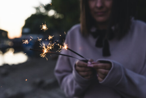 Young woman holding sparklers in the evening - UUF14851
