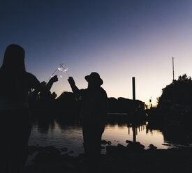 Silhouette of people at the riverside holding sparklers in the evening - UUF14857