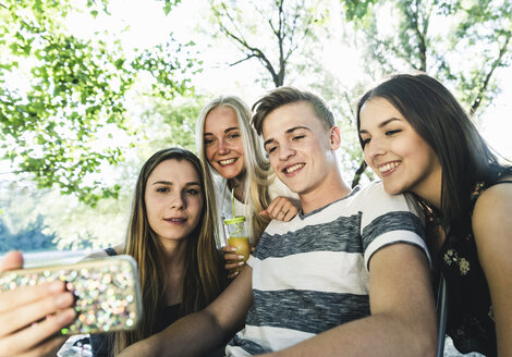 Group of smiling friends looking at cell phone outdoors - UUF14866