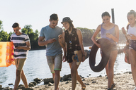 Group of friends with cell phones walking at the riverside - UUF14896
