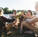 Group of happy friends sitting at the riverside toasting with drinks - UUF14905