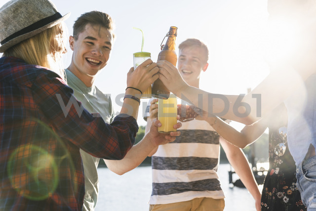 Group of happy friends standing at the riverside toasting with drinks - UUF14908 - Uwe Umstätter/Westend61