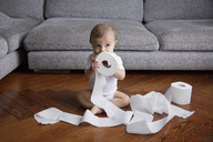 Baby boy with blond hair sitting on hardwood floor, playing with toilet paper rolls. - MINF04274