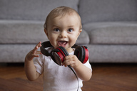 Baby boy with blond hair sitting on hardwood floor, playing with headphones. - MINF04277