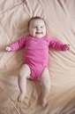 High angle view of smiling baby girl wearing pink onesie lying on a bed. - MINF04331