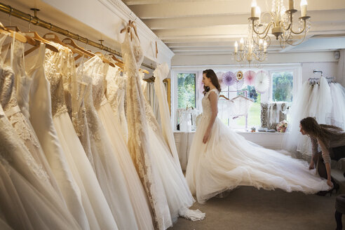 Rows of wedding dresses on display in a specialist wedding dress shop. A young woman trying on a wedding dress with a long train. - MINF04382