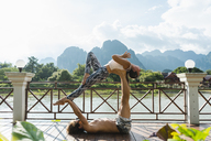 Laos, Vang Vieng, Young couple doing acro-yoga on a terrace - AFVF01218
