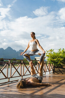 Laos, Vang Vieng, Young couple doing acro-yoga on a terrace - AFVF01221