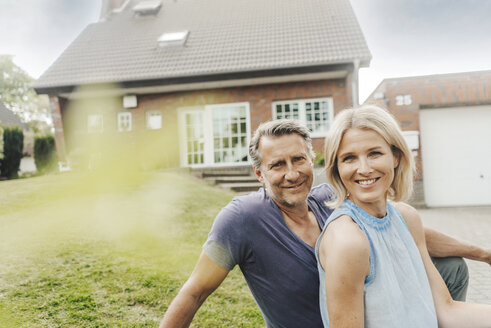 Portrait of smiling mature couple sitting in garden of their home - JOSF02438