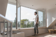 Mature man standing at the window in empty room - JOSF02441