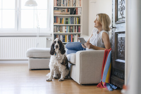 Smiling mature woman with dog lying on couch at home holding tablet - JOSF02447