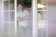 Laughing mature man standing at French window - JOSF02462